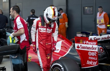 Ferrari's German driver Sebastian Vettel walks from his car after the qualifying session at the Silverstone circuit in Silverstone on July 4, 2015 ahead of the British Formula One Grand Prix. Lewis Hamilton took pole ahead of teammate Nico Rosberg with Felipe Massa in third place.  AFP PHOTO / OLI SCARFF