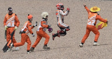 Repsol Honda Team's Spanish rider Marc Marquez (2nd R) celebrates winning the MotoGP Grand Prix of Germany at the Sachsenring Circuit on July 12, 2015 in Hohenstein-Ernstthal, eastern Germany. Repsol Honda Team's Spanish rider Marc Marquez won the race ahead of his team-mate Spanish rider Dani Pedrosa (2nd) and Movistar Yamaha MotoGP's Italian rider Valentino Rossi (3rd). AFP PHOTO / ROBERT MICHAEL
