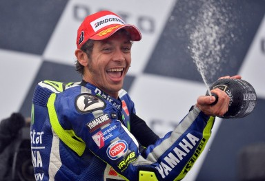 Movistar Yamaha MotoGP's Italian rider Valentino Rossi celebrates on the podium after winning the MotoGP race at the motorcycling British Grand Prix at Silverstone in Northamptonshire, England, on August 30, 2015. Valentino Rossi of Italy moved to the top of the world championship standings with his fourth victory of the season when he triumphed in the British MotoGP at Silverstone on Sunday.   AFP PHOTO / GLYN KIRK
