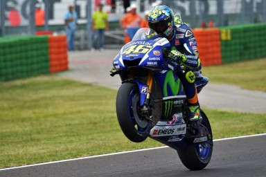 Movistar Yamaha MotoGP's Italian rider  Valentino Rossi lifts his front wheel after the Moto GP race of the San Marino MotoGP, in Misano Adriatico on September 13, 2015.   AFP PHOTO / VINCENZO PINTO
